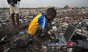 A boy on a rubbish heap looking at an old laptop