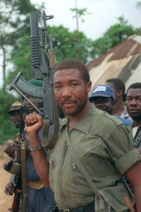 BUCHANAN, LIBERIA:  Rebel leader Charles Taylor holds his Soviet-made AK-47 assault rifle in Buchanan 29 May 1990 as he continues his march on the capital Monrovia to oust President Samuel Doe after a five-month-old insurgency. An American task force of six ships and a contingent of 2,000 marines is stationed off the coast of Liberia to evacuate some 1,100 American residents. AFP PHOTO PASCAL GUYOT (Photo credit should read PASCAL GUYOT/AFP/Getty Images)